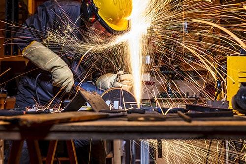 Arbeiter für Mtall Bearbeitung Fräsen des Materials mit Funken und Schutzhelm am Arbeitstisch