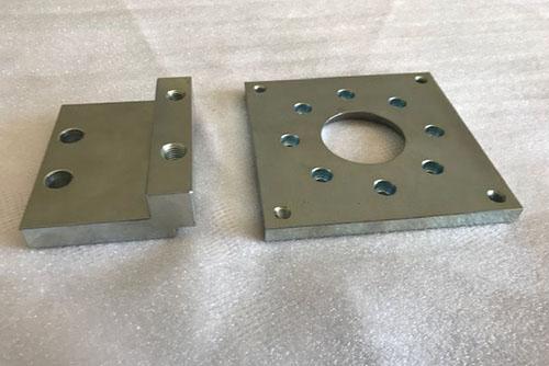 Bauteile aus Metall Metallbauteile mit großem Loch in der Mitte und Löchern außenherum und mit Aufsatz
